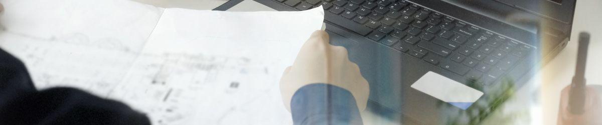 Notebook und Hand von schräg oben mit eVergabe Software