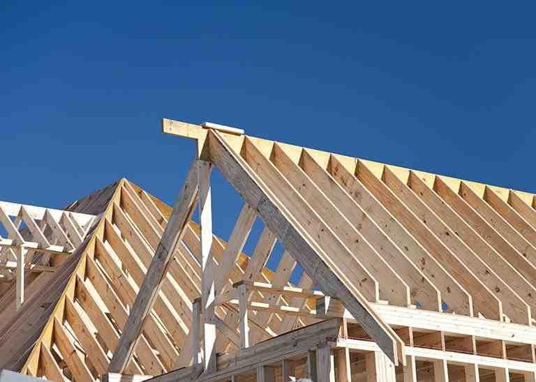 Rohbau Dachstuhl aus Holz vor blauem Himmel