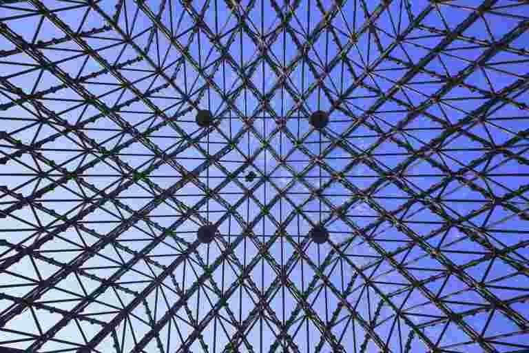 Feine gitterartige Metallstruktur eines Gebäudes vor blaunem Himmel