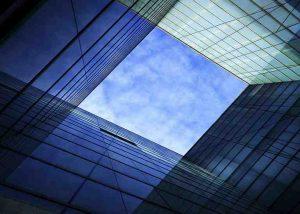 Blick auf blauen Himmel zwischen Glasgebäuden