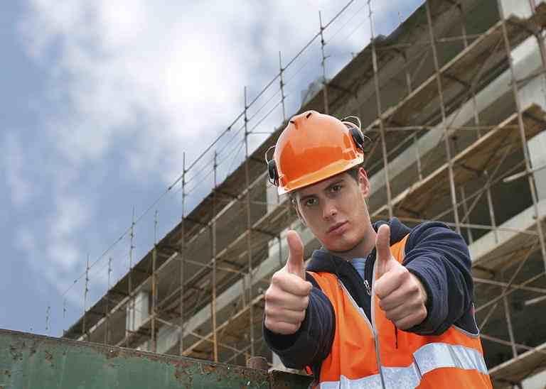 Bauarbeiter vor Baustelle mit beiden Daumen nach oben