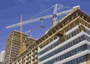 Bürogebäude im Bau mit Kran und blauem Himmel