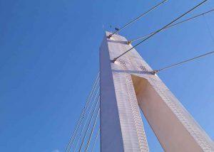Skulpturhafter Brückenpfeiler von unten mit blauem Himmel