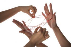4 Hände vor weißem Hintergrund mit Schnur Spiel