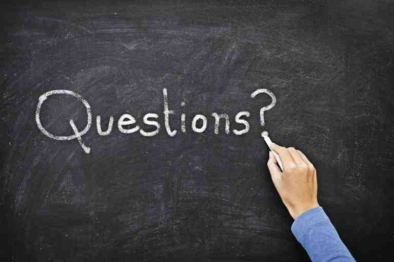 Hand schreibt mit Kreide Questions auf Tafel