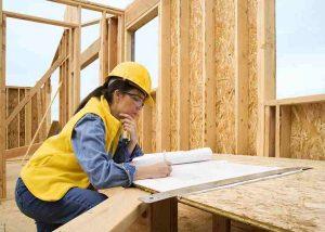 Frau mit Helm auf Holzhaus Baustelle mit Plan