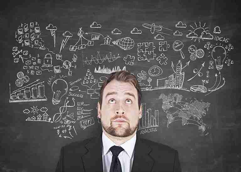Mann in schwarzem Anzug vor Tafel mit Hinweisen