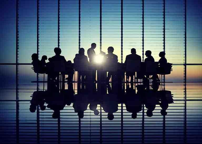 Personen in Anzügen in modernem Büro gegen die Sonne