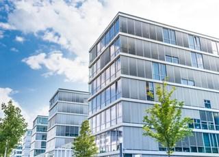 Bürogebaude bei blauem Himmel mit Wolken