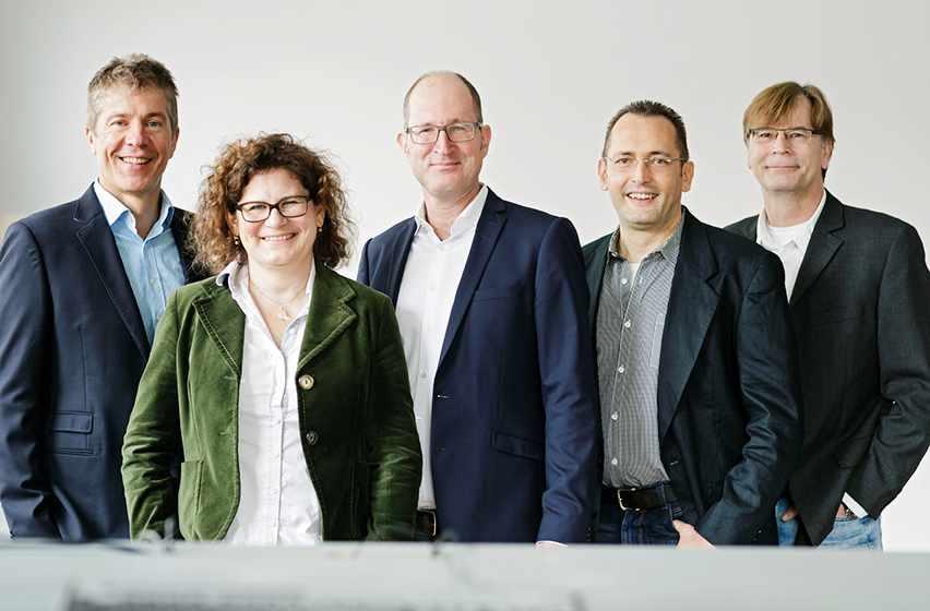 Foto 5 Personen vor grauer Wand