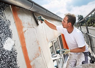Maler weißem in T-Shirt beim streichen einer Mauer