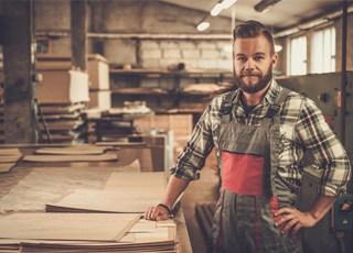 Handwerker mit Schürze vor Werkbank in Werkstatt