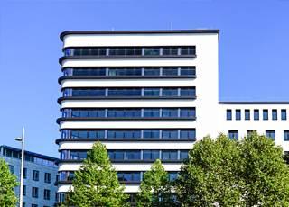 Großes Bürogebäude mit Bäumen und blauem Himmel