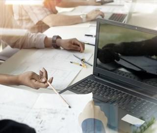 Bürotisch Arbeitsbild mit Unterlagen, Laptop und Händen