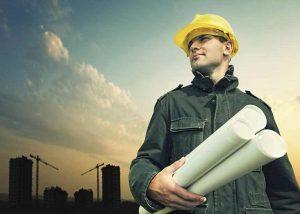 Mann mit Bauhelm und Plänen
