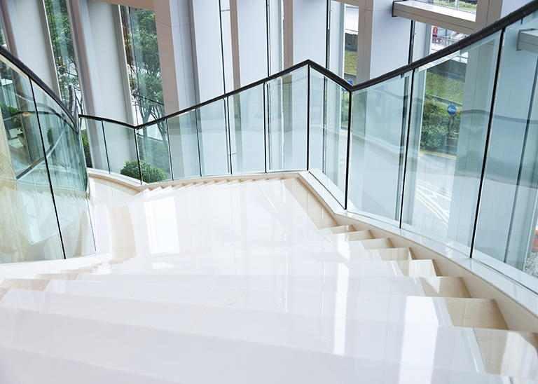 Moderne Treppe mit Glasgeländer sauber glänzend